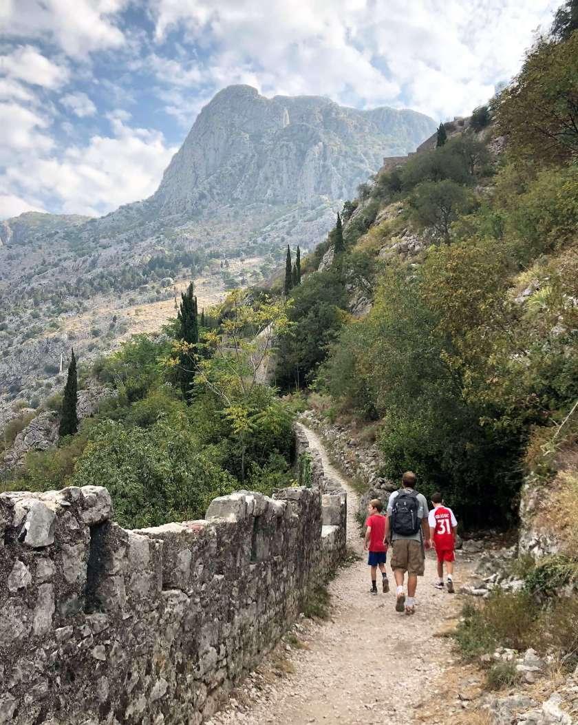 family travel climbing the city walls of Kotor, Montenegro